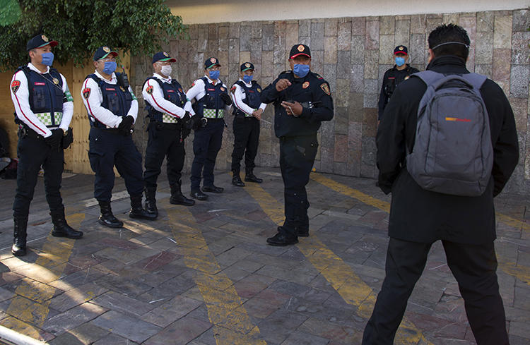 Police officers are seen in Mexico City on May 16, 2020. An unidentified man recently threatened to bomb the Mexico City offices of the Reforma newspaper. (AFP/Claudio Cruz)