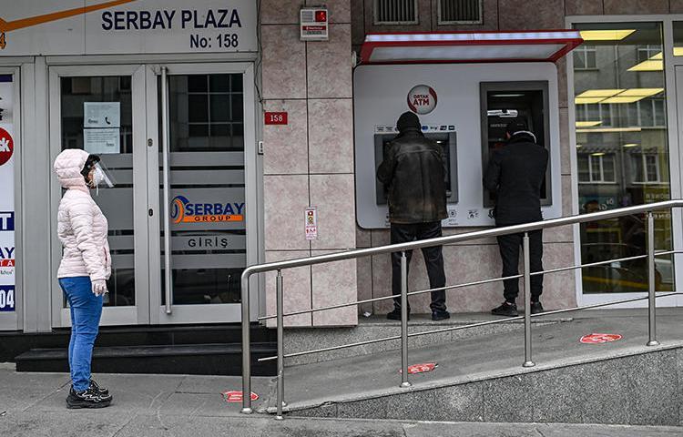 21 Nisan 2020 günü çekilen bu fotoğrafta İstanbul'da bir bankanın önündeki insanlar görülüyor. Türkiye kısa süre önce ekonomi haberciliğini kısıtlayabilecek bir finans yönetmeliğini yürürlüğe koydu. (AFP/Ozan Köse)