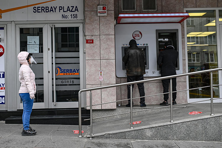 People are seen outside a bank in Istanbul, Turkey, on April 21, 2020. Turkey recently passed a financial regulation that may restrict economic reporting. (AFP/Ozan Kose)