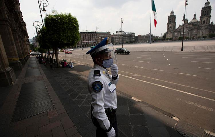 A police officer is seen in Mexico City on April 25, 2020. The Mexican Interior Secretariat recently threatened two news companies over their coronavirus coverage. (AP/Fernando Llano)
