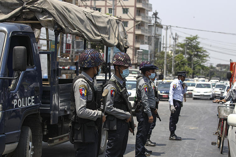 Police officers are seen in Yangon, Myanmar, on April 17, 2020. Editor Khaing Mrat Kyaw is facing terrorism charges and is in hiding. (AP/Thein Zaw)