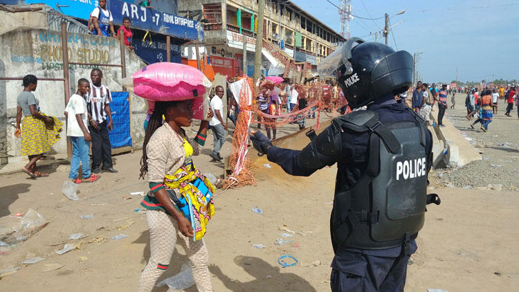 A police officer clears shoppers from a market on the first day of lockdown to stop the spread of COVID-19 disease in Monrovia, Liberia, on April 11, 2020. The government says the right to free expression is suspended during the state of emergency. (Reuters/Derick Snyder)