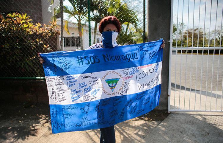 Una manifestante sostiene una bandera nacional durante una protesta contra el gobierno del presidente Daniel Ortega en Managua, Nicaragua, el 25 de febrero de 2020. YouTube ha censurado a medios independientes de noticias luego de denuncias de derecho de autor por parte de medios propiedad de Ortega. (Reuters/Oswaldo Rivas)