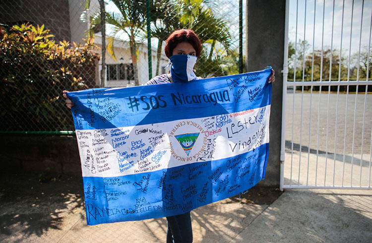 A protester holds a national flag during a demonstration against President Daniel Ortega's government in Managua, Nicaragua, on February 25, 2020. YouTube has censored independent Nicaraguan news outlets after copyright complaints from Ortega-owned media. (Reuters/Oswaldo Rivas)