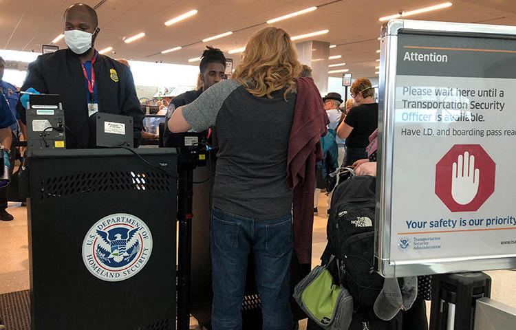 A U.S. Department of Homeland Security officer checks passports in Fort Lauderdale, Florida, on March 15, 2020. The department recently imposed new restrictions on Chinese nationals working as journalists in the United States. (Reuters/Teresa Barbieri)