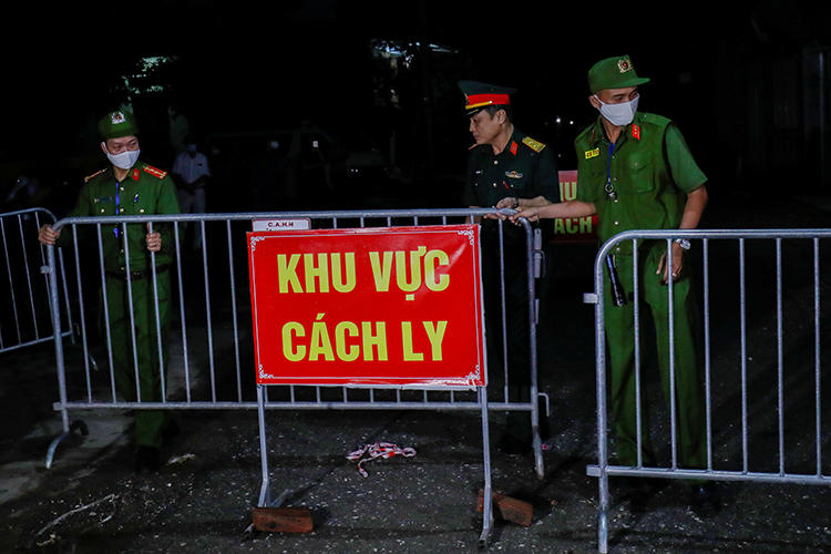 Police and soldiers are seen in Dong Cuu village, outside Hanoi, Vietnam, on May 14, 2020. Hanoi authorities recently arrested journalists Nguyen Tuong Thuy and Pham Chi Thanh. (Reuters/Nguyen Huy Kham)