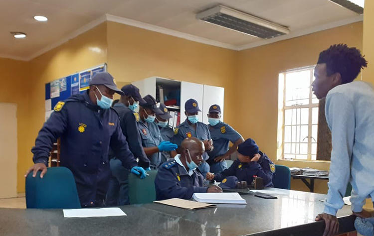 Police officers are seen in the Ficksburg police station. Police recently beat and charged journalist Paul Nthoba after he photographed them enforcing the COVID-19 lockdown. (Photo: Paul Nthoba)