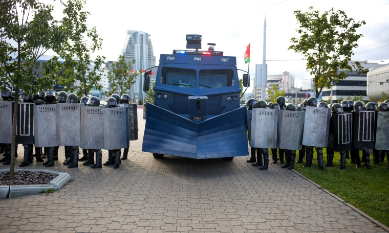 A large vehicle flanked by police officers holding shields blocks a city street.