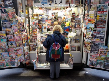 A woman facing away from the camera looks at a large display of magazines and newspapers.