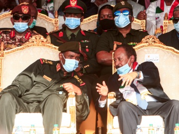 A man in military uniform and a coronavirus mask seated in an elaborate chair leans over to talk with a man in a suit and a coronavirus mask in the neighboring chair.