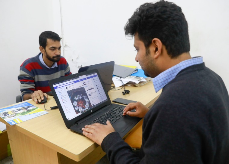 Two men use laptops on opposite sides of a desk
