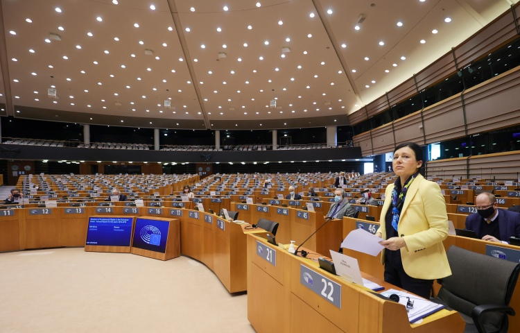 A woman in a yellow jacket stands at a row of work benches in the European Parliament.