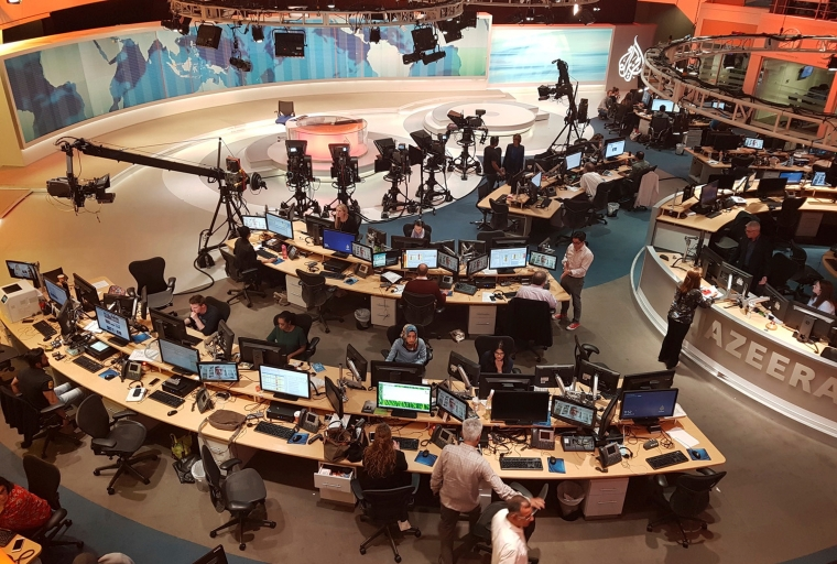 Journalists are shown working at their desks behind the scenes of a TV news studio.
