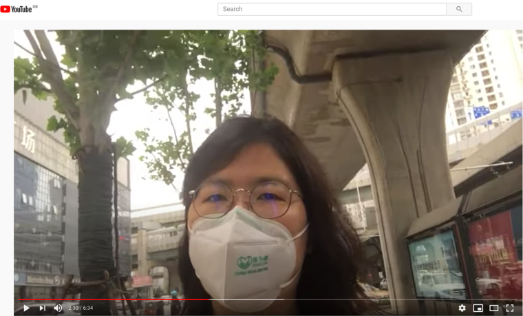 A woman in a face mask is seen addressing the camera in a YouTube vide.
