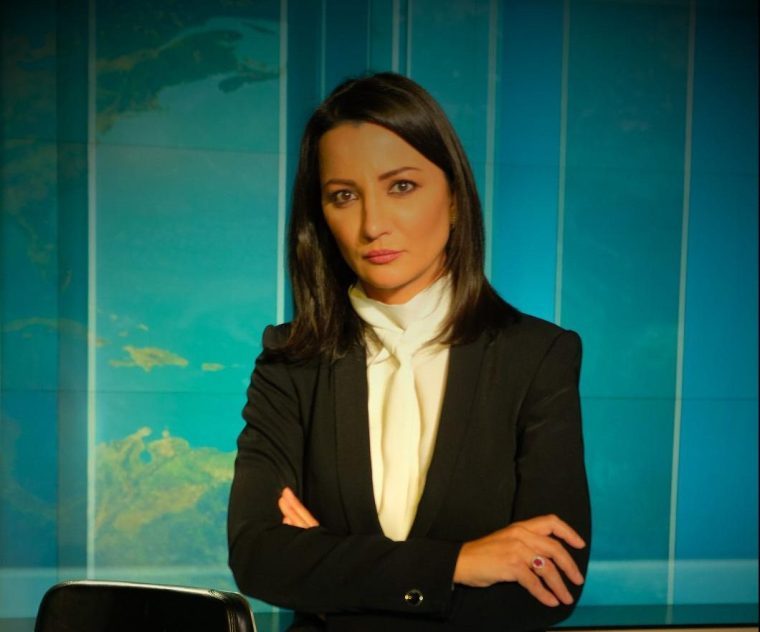 Portrait of Ghada Oueiss facing camera with arms folded in a newsroom