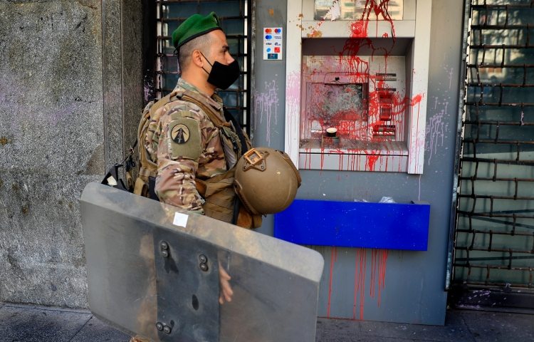 A soldier wearing a mask is shown in profile passing an ATM machine covered in red paint.
