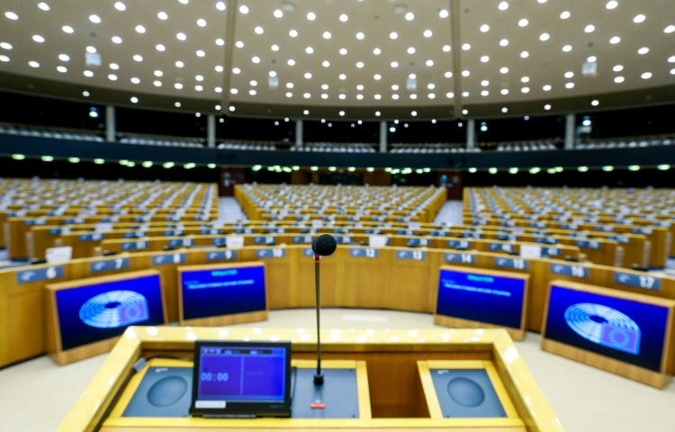 A lectern is shown against a backdrop of empty desks set up for a parliamentary meeting.