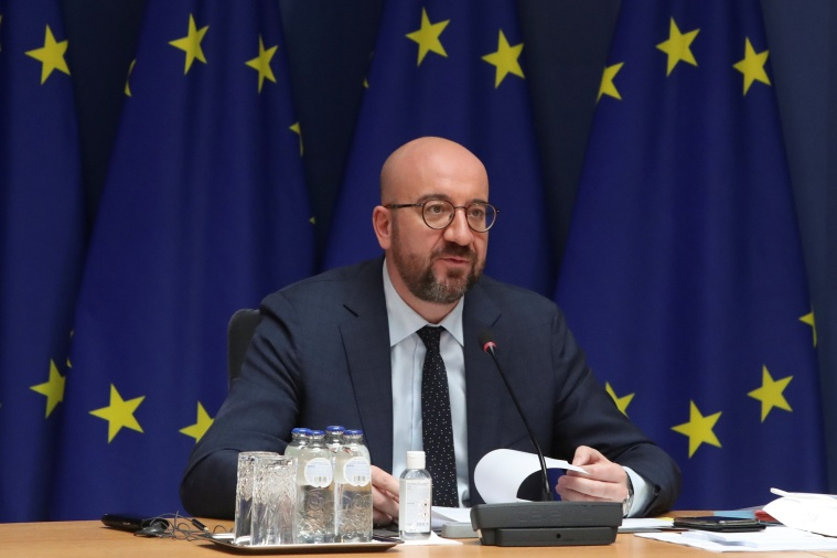 A seated man in a suit speaks into a microphone against a backdrop of the EU flag.
