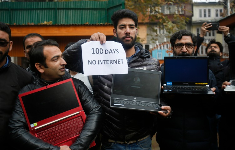 """A group of men are pictured holding powered off laptops and a placard reading """"100 days no internet."""""""