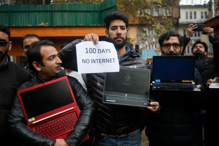 "A group of men are pictured holding powered off laptops and a placard reading ""100 days no internet."""