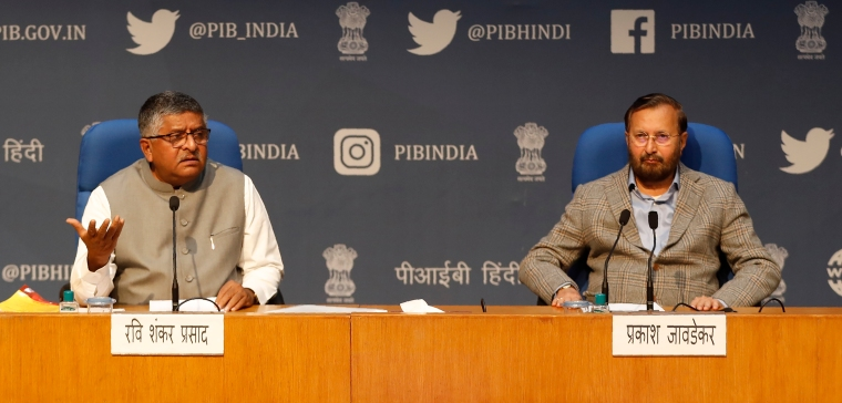 Two men sit at a podium against a backdrop illustrated with logos of social media companies.