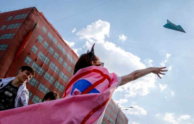 A woman throws a paper plane into the blue sky.