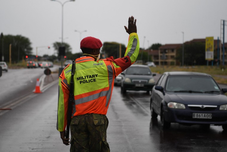 An armed officer on a street raises his hand to stop cars.
