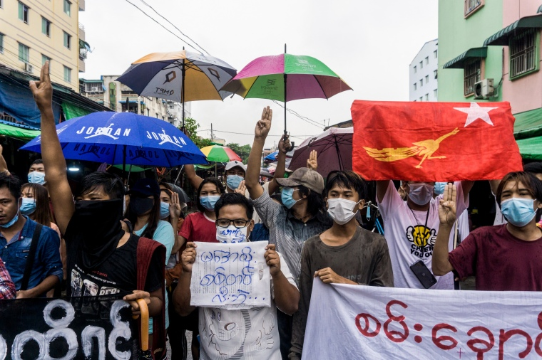 A group of people holding protest signs and umbrellas gather in a city street.