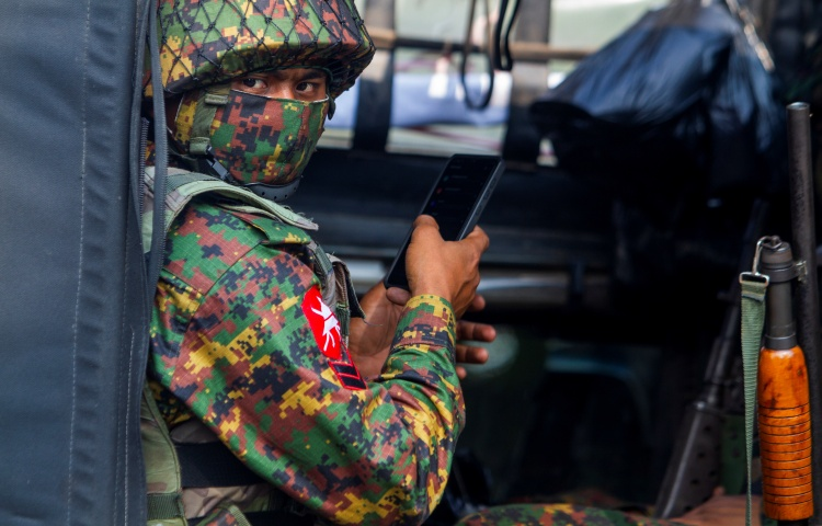 A man in military fatigues and a face mask holding a cell phone in his hand looks at the camera.