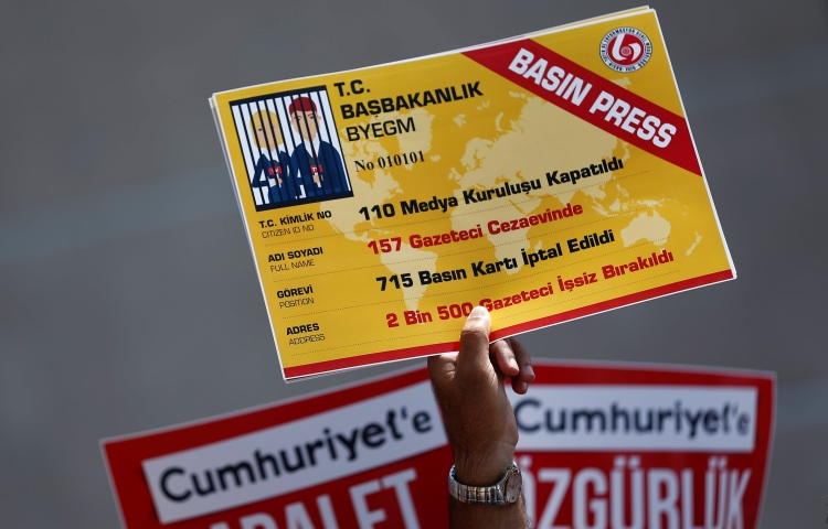 A raised hand holds a large ID card showing journalists in jail in place of a photo.