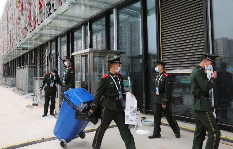Men in uniforms and masks stand outside a large modern building..